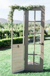 A clever frame to the ceremony- rather than an arch: two rustic doors. Photo by Katie Jackson