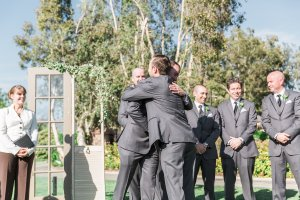 I love it when the groomsmen hug it out with the groom as they walk up the aisle to stand alongside him. Photo by Katie Jackson