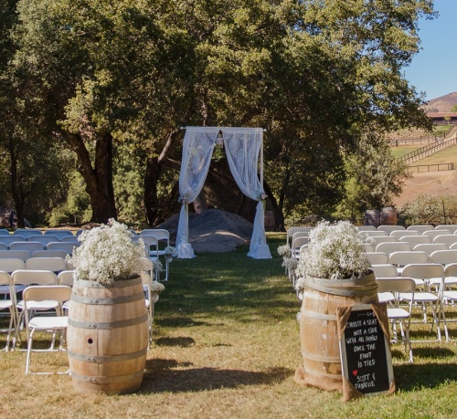 Single frame with gauzy drapes frame a solid grounding boulder amongst the beauty of the trees, at Milagro Winery. The groomsmen crafted the frame themselves so that it held solidly on the ground. Photo by Dinela Photography